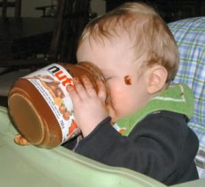 un enfant mangeant du Nutella directement au pot