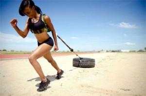 une femme avec un harnais tirant un énorme pneu